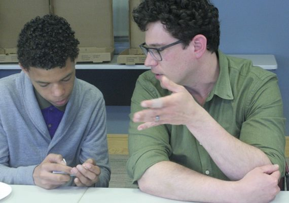 An adult speaking to a teenage boy in a calming way