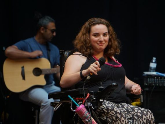 Jessica singing on stage with a microphone, with a person playing the guitar in the background