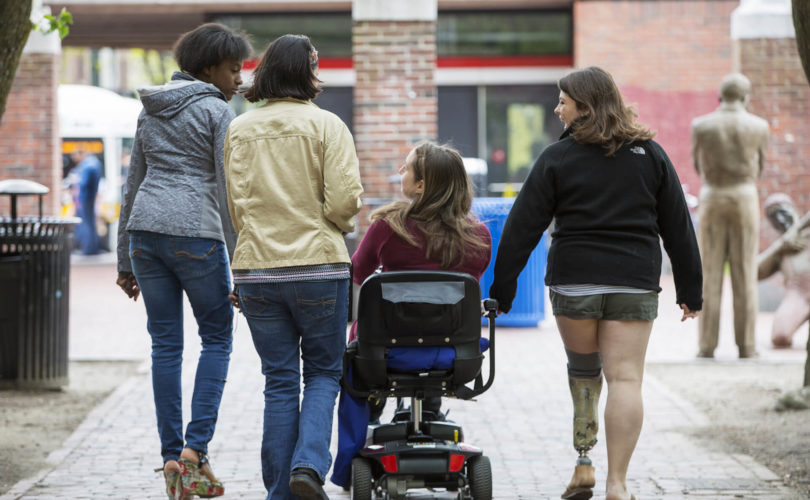 Four girls with different disabilities walking together towards a subway station, laughing