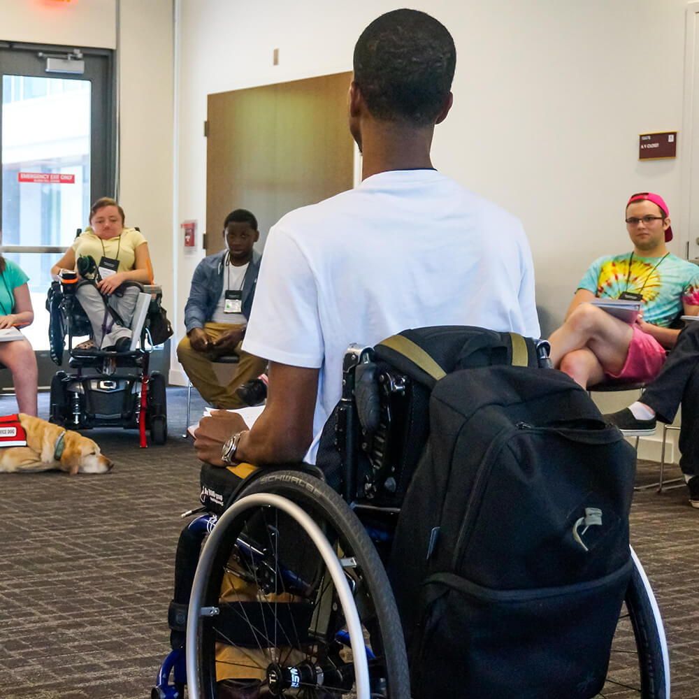 A young man in a wheelchair leads a team of professionals