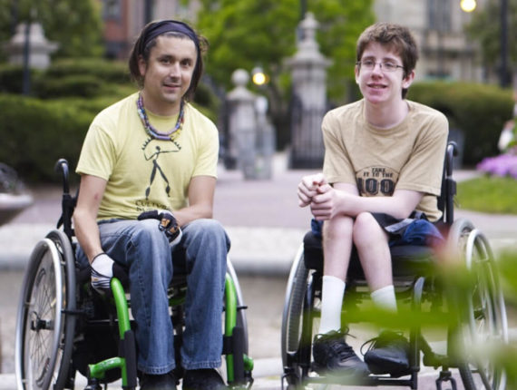 A mentor and mentee in wheelchairs enjoy an afternoon in the park together