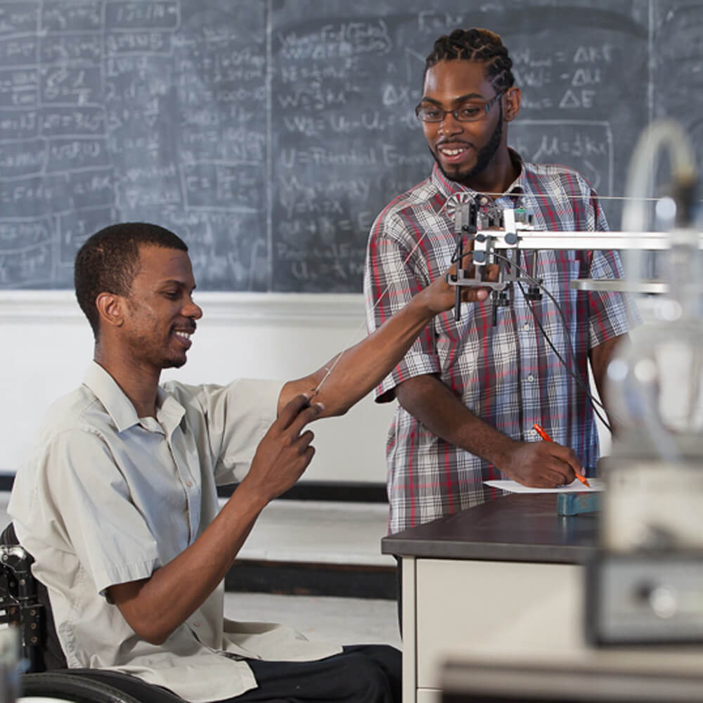 Two high school students work on a chemistry experiment