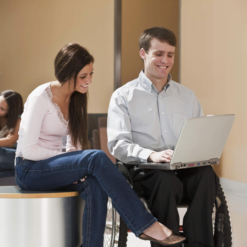 Two students brainstorming in front of laptop