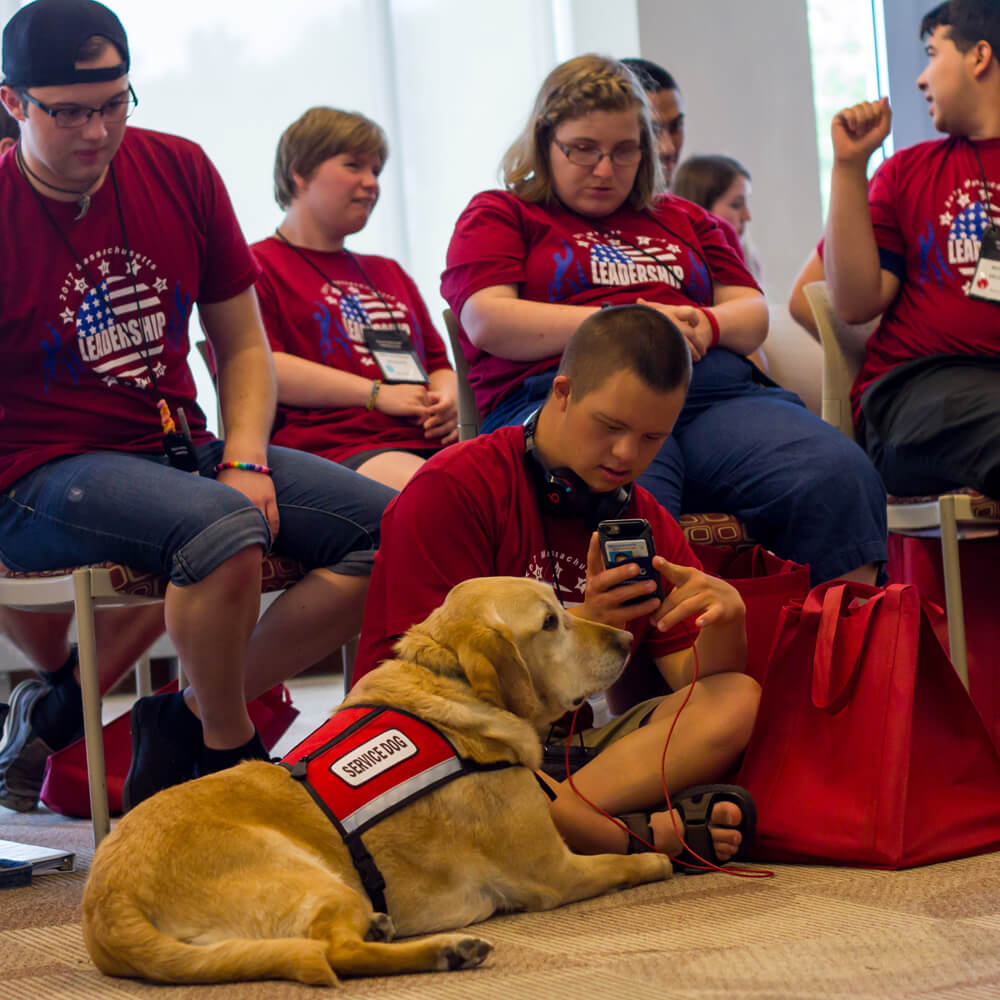 Youth Leadership Forum - A group of students and a service dog meeting at a leadership conference