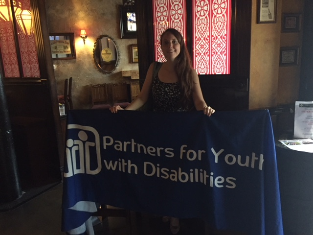 Kristin holding the PYD tablecloth banner at the Lansdowne Pub