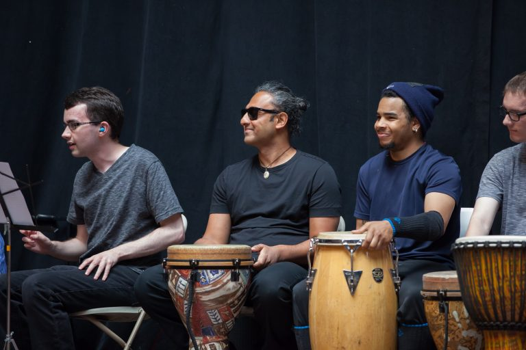 Deep sitting in front of a drum, smiling
