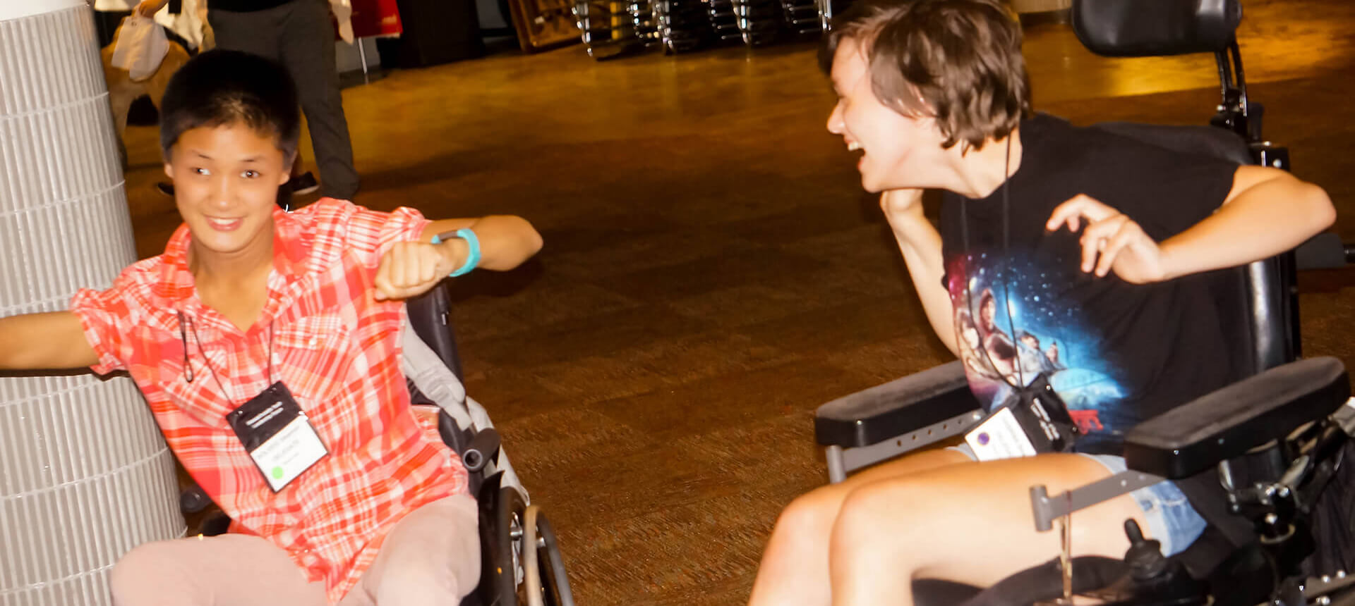 Two disabled youth in wheelchairs having a laugh together