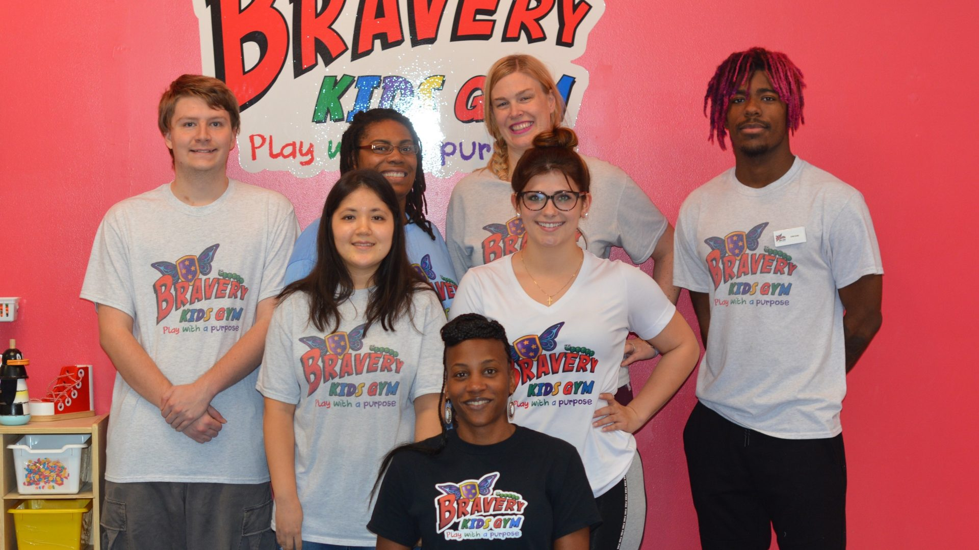 Marcella sitting with the staff of the Bravery Kids Gym in front of a wall with their logo on it