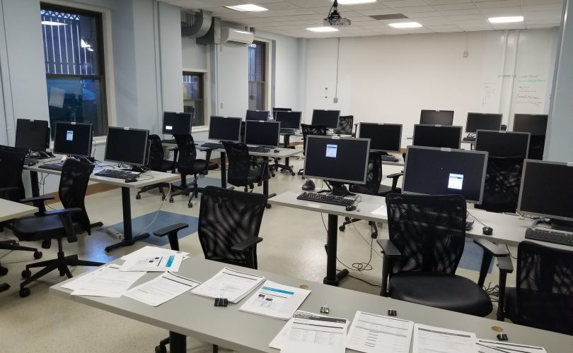 A classroom-style room with rows of tables and chairs, with computers at more desk spots.