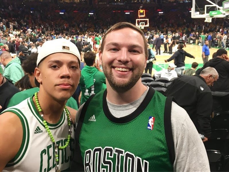 Matt and his mentee pose together in front of the basketball court at the TD Garden, both wearing Celtics gear.