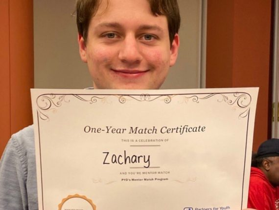 Zachary, a PYD youth smiles for a photo as he holds up his one year match certificate