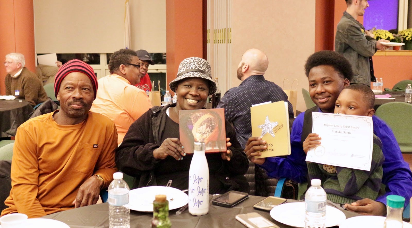 Photo of spirit award winner Franklin and three of his family members pose for a photo smiling and holding up Franklin's certificate as they sit down at a table
