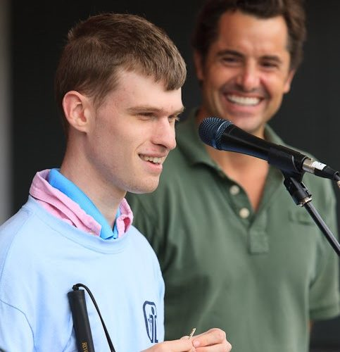 Tyler stands in front of a microphone smiling wearing a blue and pink shirt. A man stands behind him smiling wearing a green shirt.
