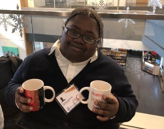 Donasia sits at a table at the Trade Show and holds 2 mugs that she made
