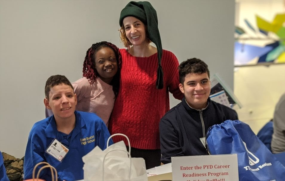 Our Career Readiness Coordinator Neda smiles for a photo with three PYD youth sitting at a table in front of trade show items at State Street