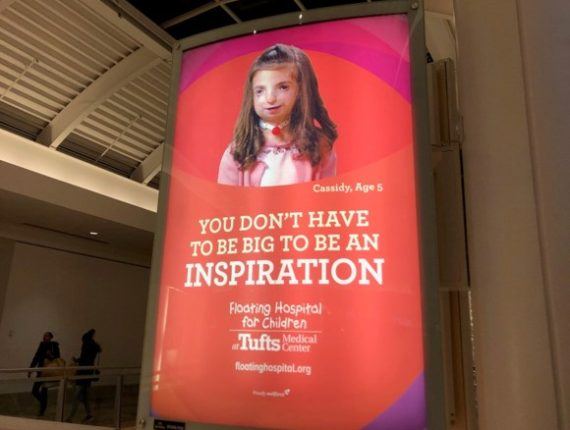 "The image is an advertisement from Tufts Medical Center of a child with a visible disability that reads ""You don't have to be big to be an inspiration. Floating Hospital for Children at Tufts Medical Center"""