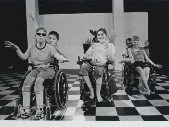 A black and white photo of Sarah (middle) along with other PYD members in wheel chairs