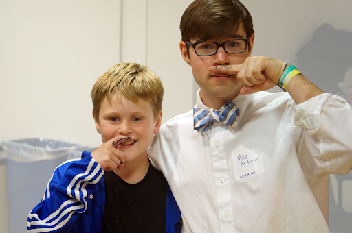 Brody (left) and Mike (right) stand side by side with drawn on mustaches.
