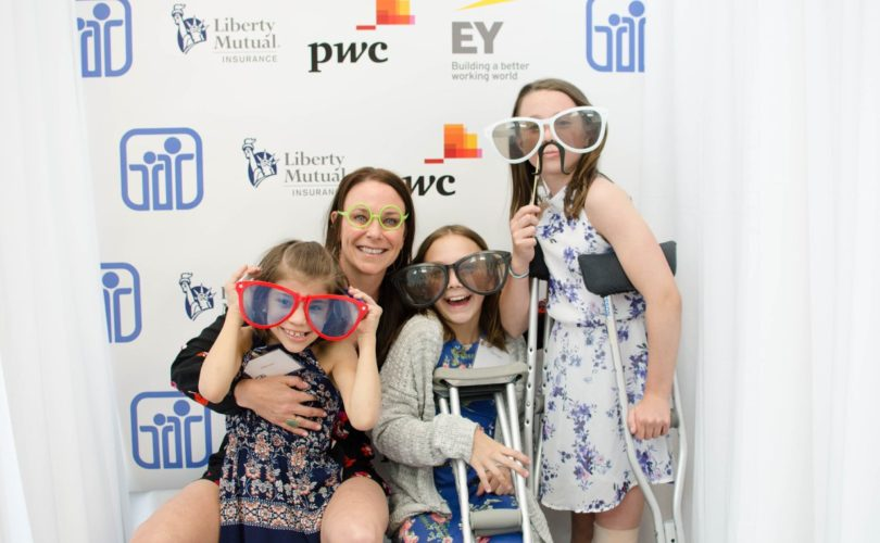 3 youth smiling posing with an adult wearing fun photo booth glasses, two children are using crutches