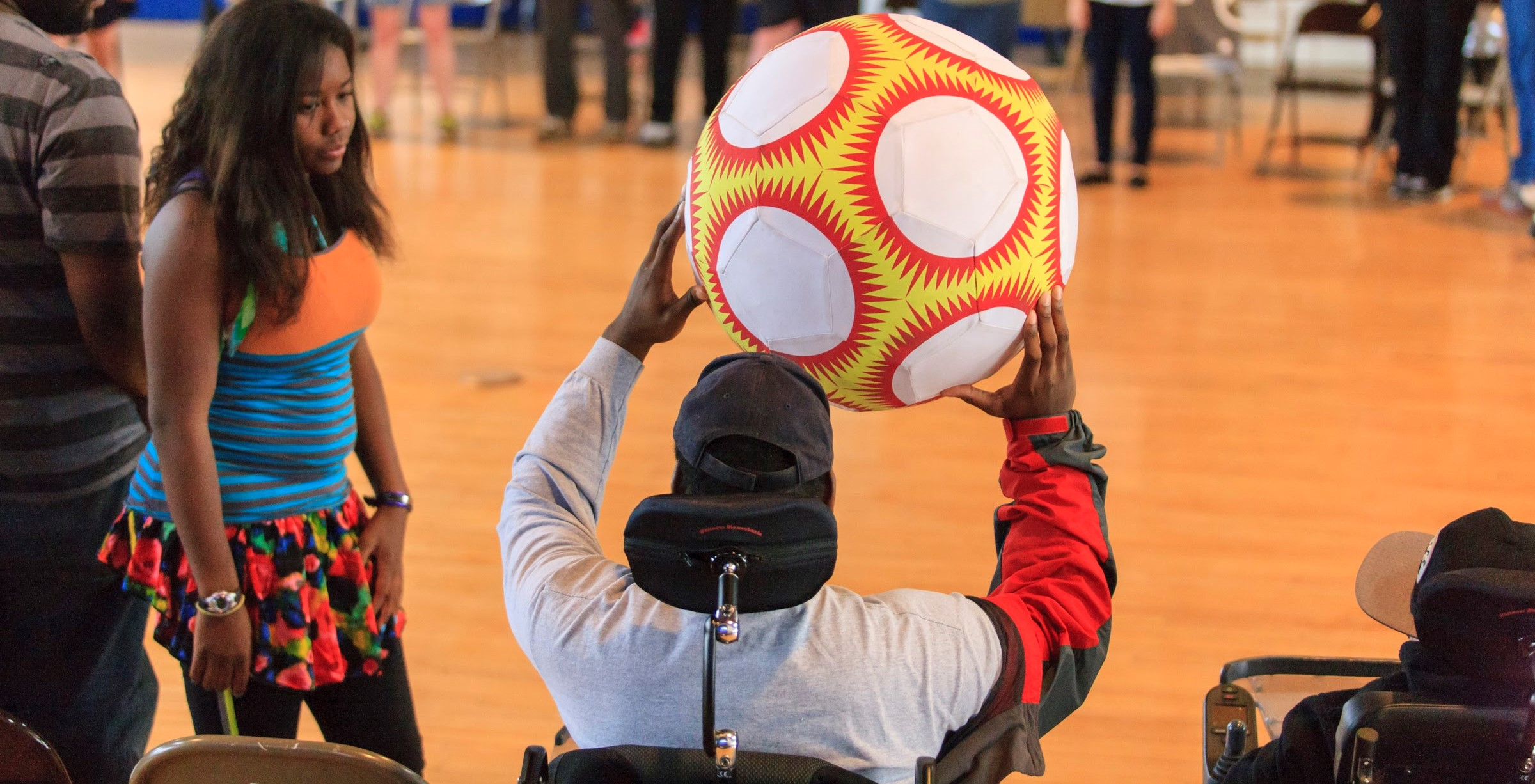 Man in wheel chair is holding up an orange and red ball. Another youth is standing next to them and looking at them.