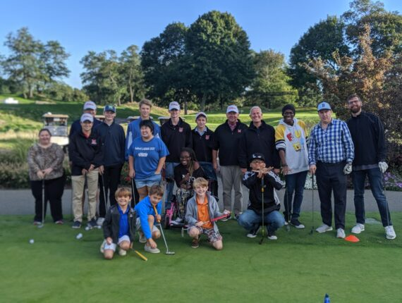 A local high school golf team posing for a picture with a group of PYD participants on a putting green